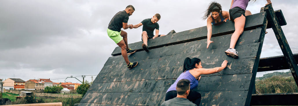people climbing over an obstacle