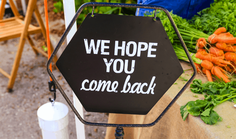 Store owner sign that says 'we hope you come back'.